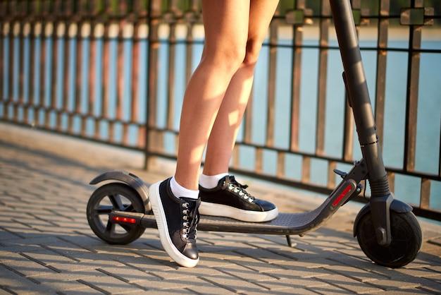 Tiener middelbare school meisje met elektrische scooter in de buurt van het water