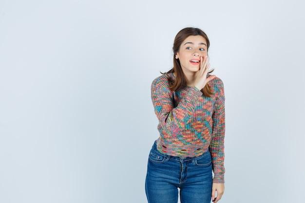 Tiener mooi meisje met hand in de buurt van mond, wegkijkend in trui, spijkerbroek en nieuwsgierig, vooraanzicht.