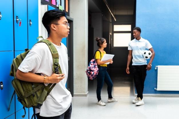 Tiener multiraciale studenten in de gang van de middelbare school in de buurt van kluisjes onderwijsconcept terug naar school