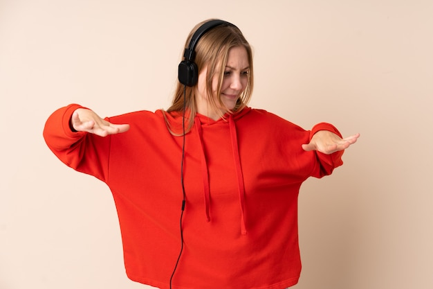 Tiener oekraïens meisje dat bij beige het luisteren muziek en het dansen wordt geïsoleerd