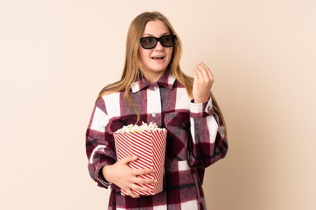 Tiener oekraïens meisje dat op beige met 3d glazen wordt geïsoleerd en een grote emmer popcorns houdt