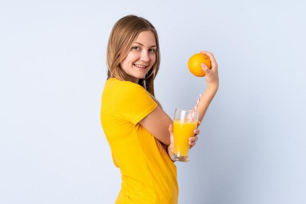 Tiener oekraïense vrouw die op blauwe ruimte wordt geïsoleerd die een sinaasappel en een jus d'orange houdt