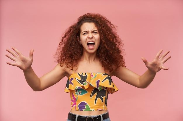 Tiener, ongelukkig uitziende vrouw met gember krullend haar, gekleed in kleurrijke off-shoulder blouse