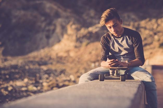 Tiener op het strand zittend op een muur die zijn telefoons gebruikt met zijn skateboard - jongen met een spijkerbroek gericht op het sociale of het spelen van videogames