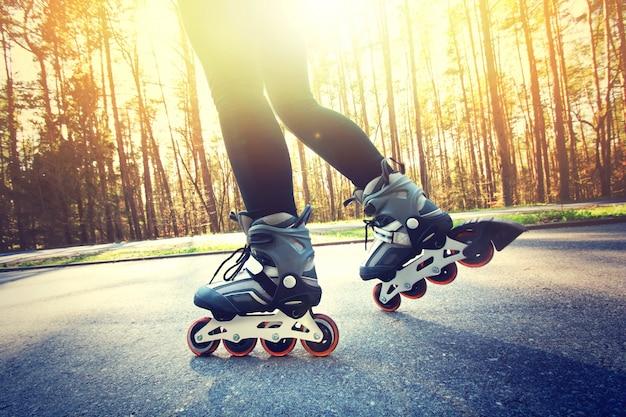Tiener op roller skates in de zomer.