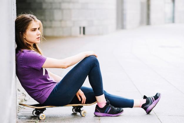 Tiener op skateboard in de buurt van de muur