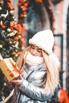 Tiener pakt een geschenk uit bij de kerstboom