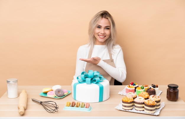 Tiener patissier met een grote cake in een tafel die handen naar de zijkant uitstrekt om uit te nodigen om te komen