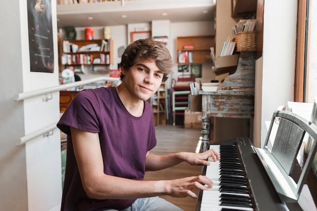 Tiener pianospelen en camera kijken
