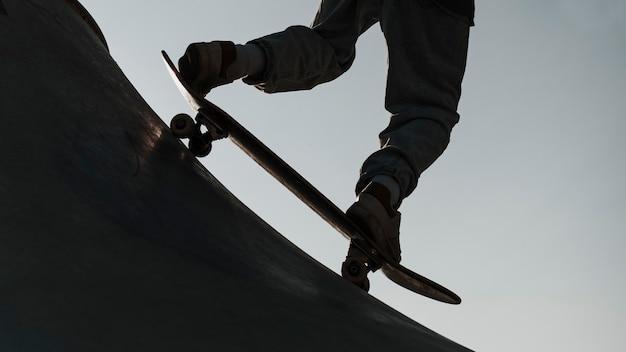 Tiener plezier met skateboard bij het park silhouet