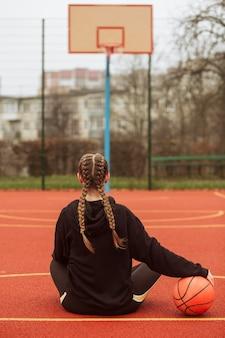 Tiener poseren op het basketbalveld