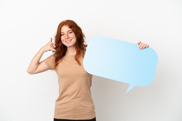 Tiener roodharig meisje geïsoleerd op een witte achtergrond met een lege tekstballon en telefoon gebaar