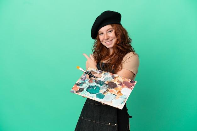 Tiener roodharige artiest met een palet geïsoleerd op een groene achtergrond die terug wijst