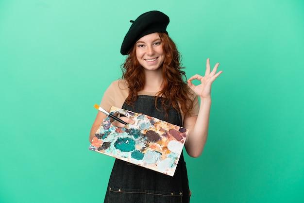 Tiener roodharige artiest met een palet geïsoleerd op een groene achtergrond met ok teken met vingers