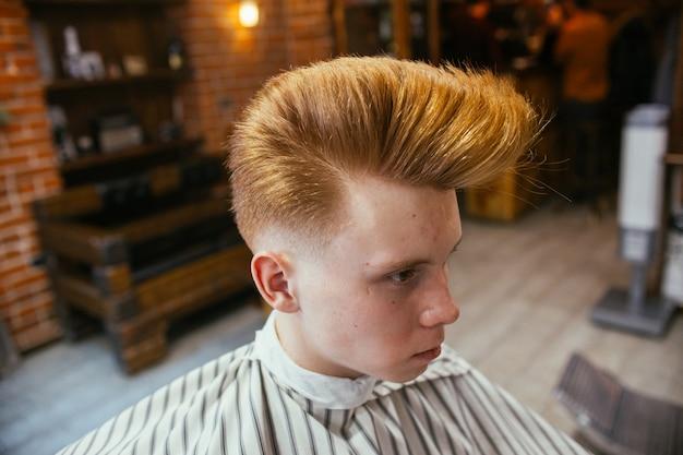 Tiener roodharige jongen kapsels kapper in de kapper. modieus stijlvol retro kapsel