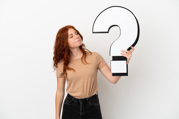 Tiener roodharige meisje geïsoleerd op een witte achtergrond met een vraagteken pictogram en twijfels
