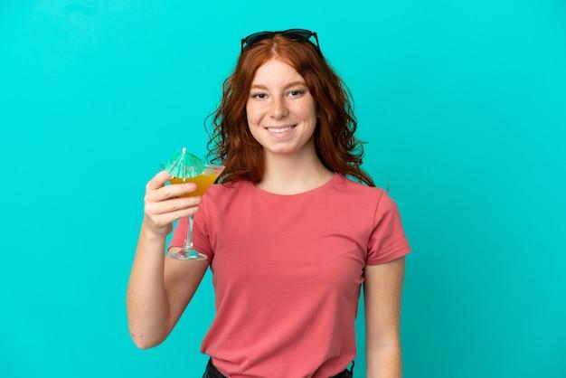 Tiener roodharige meisje met cocktail geïsoleerd op een blauwe achtergrond glimlachend veel