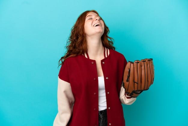 Tiener roodharige meisje met honkbal handschoen geïsoleerd op blauwe achtergrond lachen