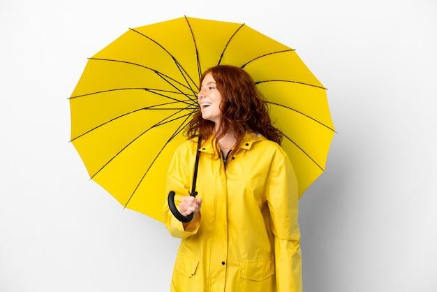 Tiener roodharige meisje regendichte jas en paraplu geïsoleerd op een witte achtergrond lachen in laterale positie