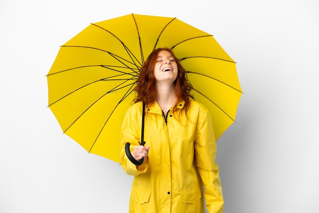 Tiener roodharige meisje regendichte jas en paraplu geïsoleerd op een witte achtergrond lachen
