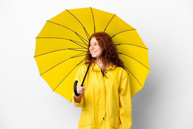 Tiener roodharige meisje regendichte jas en paraplu geïsoleerd op een witte achtergrond op zoek naar de kant