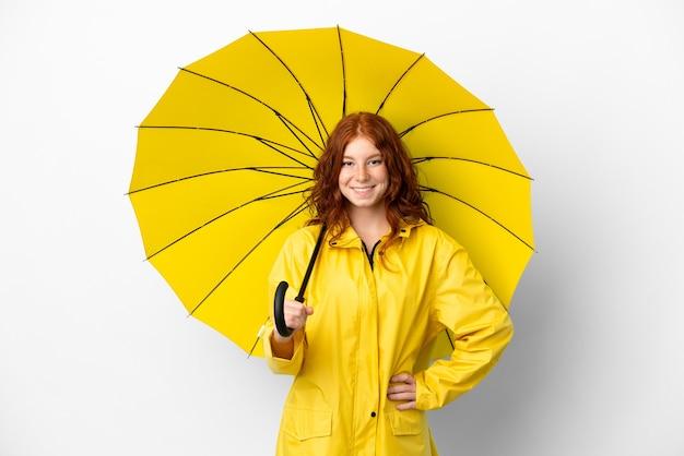 Tiener roodharige meisje regendichte jas en paraplu geïsoleerd op een witte achtergrond poseren met armen op heup en lachend