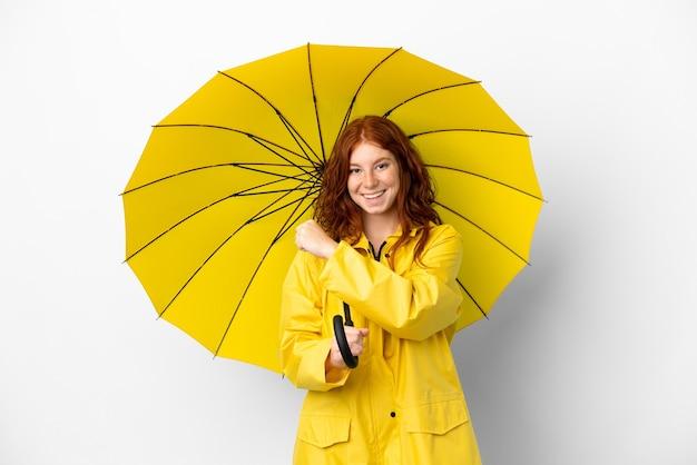 Tiener roodharige meisje regendichte jas en paraplu geïsoleerd op een witte achtergrond vieren een overwinning