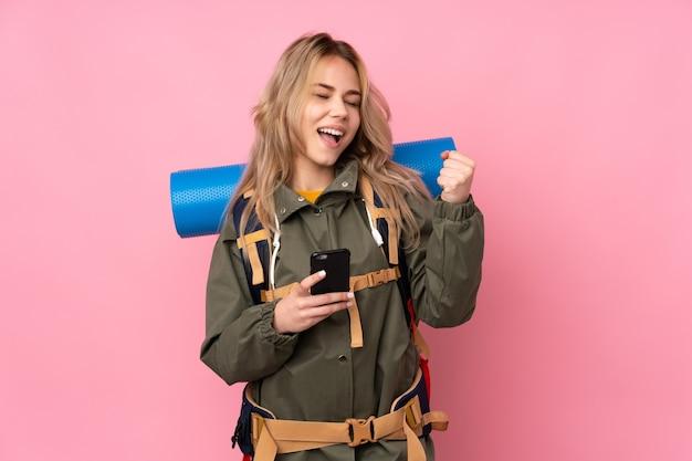 Tiener russisch bergbeklimmer meisje met een grote rugzak geïsoleerd op roze met telefoon in overwinning positie