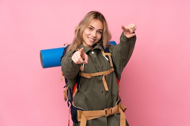 Tiener russisch bergbeklimmer meisje met een grote rugzak geïsoleerd op roze muur wijst vinger naar je terwijl lachend