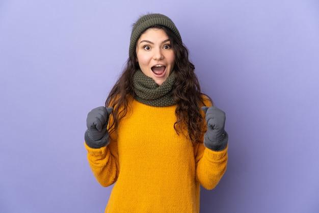 Tiener russisch meisje dat met de winterhoed op purpere muur wordt geïsoleerd die een overwinning in winnaarspositie viert
