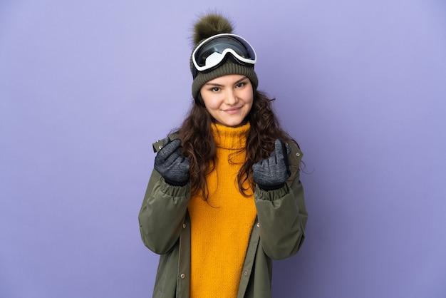 Tiener russisch meisje dat met snowboardglazen op purpere muur wordt geïsoleerd die geldgebaar maakt