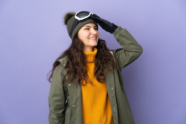 Tiener russisch meisje dat met snowboardglazen op purpere muur wordt geïsoleerd die veel glimlachen