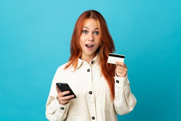 Tiener russisch meisje dat op blauwe muur wordt geïsoleerd die met mobiel koopt en een creditcard met verbaasde uitdrukking houdt