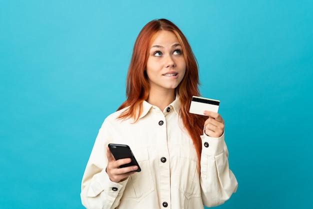 Tiener russisch meisje dat op blauwe muur wordt geïsoleerd die met mobiel met een creditcard koopt terwijl het nadenken