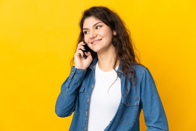 Tiener russisch meisje dat op gele muur wordt geïsoleerd die een gesprek met de mobiele telefoon met iemand houdt