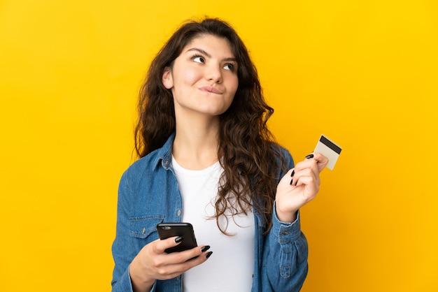 Tiener russisch meisje dat op gele muur wordt geïsoleerd die met mobiel met een creditcard koopt terwijl het nadenken