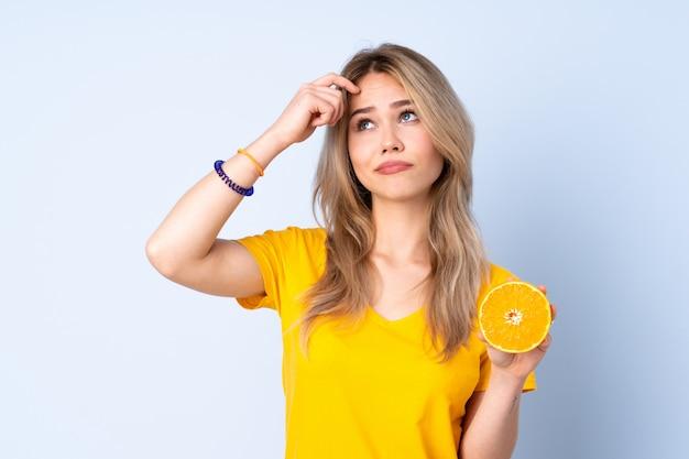 Tiener russisch meisje die een sinaasappel op blauwe muur houden die twijfels hebben en met gezichtsuitdrukking verwarren