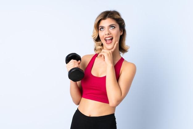 Tiener russisch meisje die gewichtheffen maken dat op blauwe muur wordt geïsoleerd die met wijd open mond schreeuwen