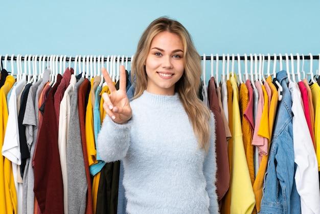 Tiener russisch meisje die kleren kopen die op blauwe muur worden geïsoleerd die en overwinningsteken glimlachen tonen