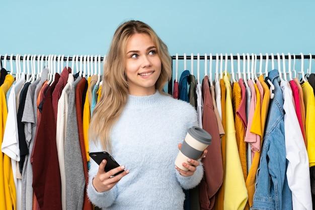 Tiener russisch meisje die kleren kopen die op blauwe worden geïsoleerd die koffie houden om mee te nemen en een mobiel terwijl zij iets denken