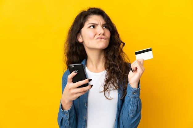 Tiener russisch meisje geïsoleerd op gele achtergrond kopen met de mobiele telefoon met een creditcard tijdens het denken
