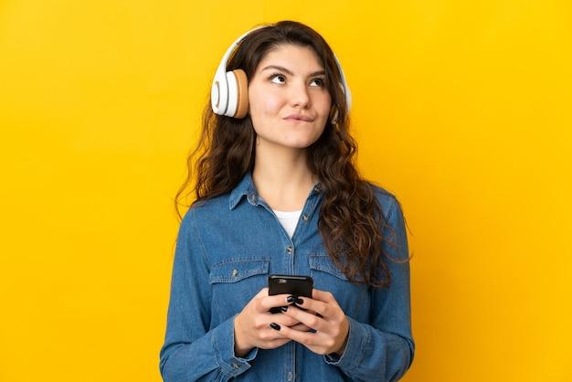 Tiener russisch meisje geïsoleerd op gele achtergrond muziek luisteren met een mobiele telefoon en denken