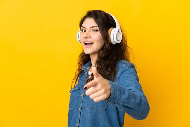 Tiener russisch meisje geïsoleerd op gele achtergrond muziek luisteren