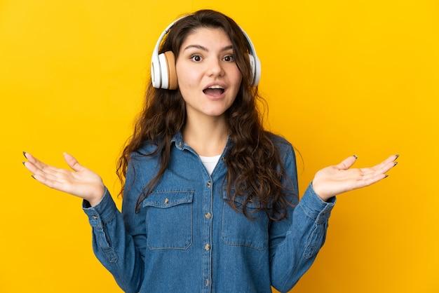 Tiener russisch meisje geïsoleerd op gele muur verrast en luisteren muziek
