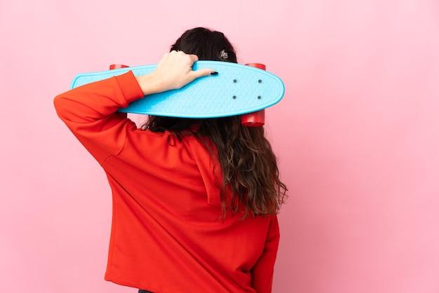 Tiener russisch meisje geïsoleerd op roze achtergrond met een skate in achterpositie