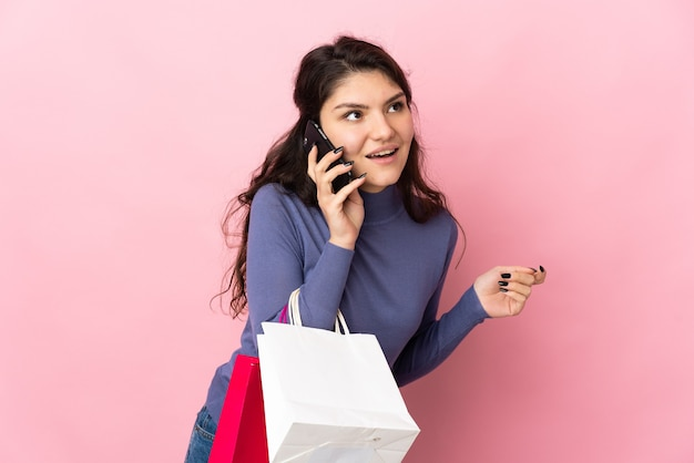 Tiener russisch meisje geïsoleerd op roze muur met boodschappentassen en een vriend bellen met haar mobiele telefoon
