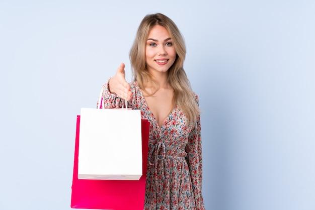 Tiener russisch meisje met boodschappentas geïsoleerd op blauwe handen schudden voor het sluiten van een goede deal