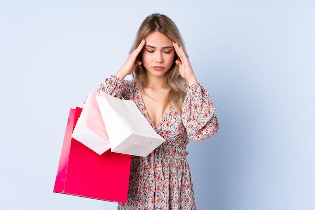 Tiener russisch meisje met boodschappentas geïsoleerd op blauwe muur met hoofdpijn
