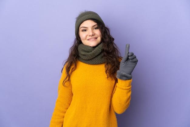 Tiener russisch meisje met de winterhoed die op purpere achtergrond wordt geïsoleerd die en een vinger in teken van het beste opheft