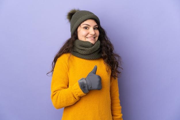 Tiener russisch meisje met de winterhoed die op purpere muur wordt geïsoleerd die een duim omhoog gebaar geeft
